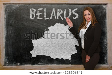 Successful, beautiful and confident young woman showing map of belarus on blackboard for presentation, marketing research and tourist advertising - stock photo