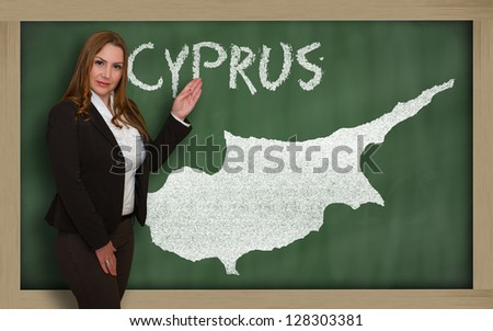 Successful, beautiful and confident young woman showing map of cyprus on blackboard for presentation, marketing research and tourist advertising - stock photo