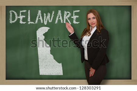 Successful, beautiful and confident young woman showing map of delaware on blackboard for presentation, marketing research and tourist advertising - stock photo