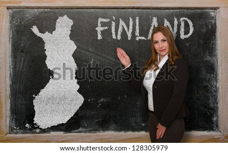 Successful, beautiful and confident young woman showing map of finland on blackboard for presentation, marketing research and tourist advertising - stock photo