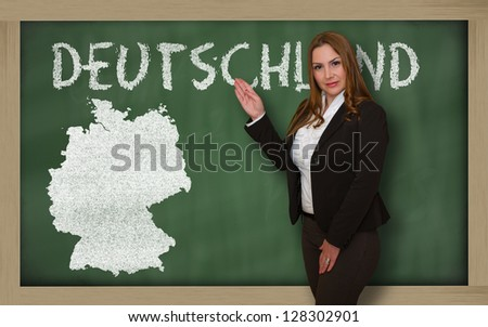 Successful, beautiful and confident young woman showing map of germany on blackboard for presentation, marketing research and tourist advertising - stock photo