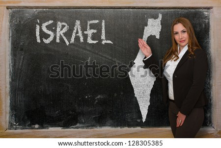 Successful, beautiful and confident young woman showing map of israel on blackboard for presentation, marketing research and tourist advertising - stock photo