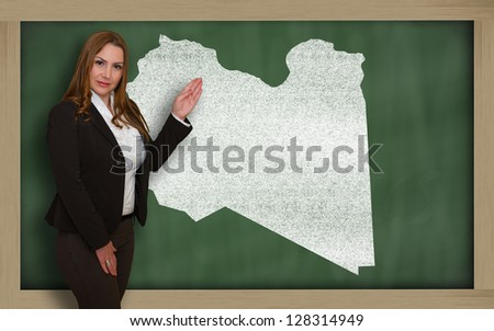 Successful, beautiful and confident young woman showing map of lybia on blackboard for presentation, marketing research and tourist advertising