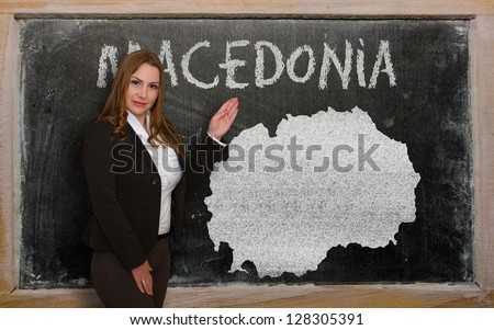 Successful, beautiful and confident young woman showing map of macedonia on blackboard for presentation, marketing research and tourist advertising - stock photo