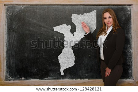 Successful, beautiful and confident young woman showing map of mozambique on blackboard for presentation, marketing research and tourist advertising