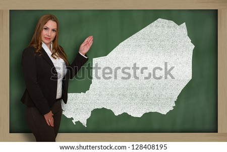 Successful, beautiful and confident young woman showing map of niger on blackboard for presentation, marketing research and tourist advertising