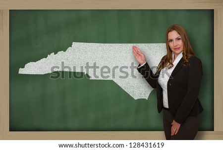 Successful, beautiful and confident young woman showing map of north carolina on blackboard for presentation, marketing research and tourist advertising