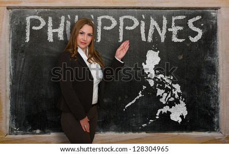 Successful, beautiful and confident young woman showing map of philippines on blackboard for presentation, marketing research and tourist advertising - stock photo