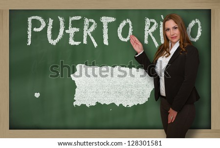 Successful, beautiful and confident young woman showing map of puerto rico on blackboard for presentation, marketing research and tourist advertising - stock photo