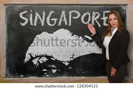 Successful, beautiful and confident young woman showing map of singapore on blackboard for presentation, marketing research and tourist advertising - stock photo