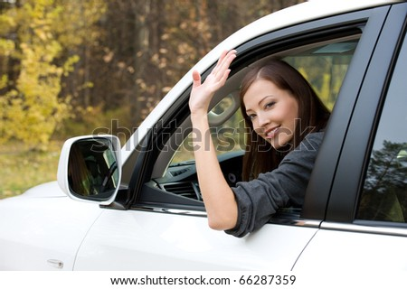 Successful beautiful young woman in the new car  - outdoors - stock photo