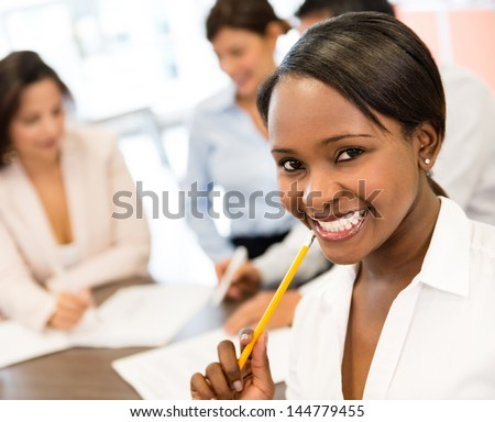 Successful black business woman at the office looking very happy - stock photo