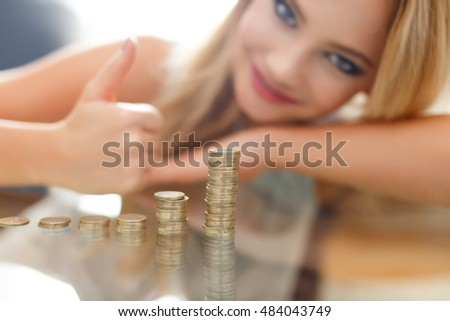 Successful blonde woman thumb up at growing euro columns, indoor closeup portrait, depth of field, saving money concept