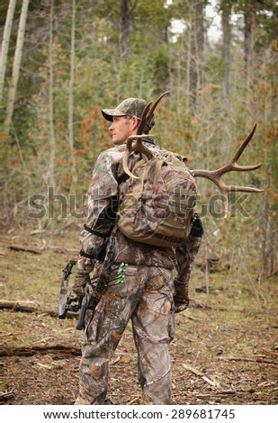 successful bow hunter hiking through woods - stock photo