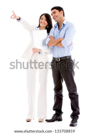 Successful business couple pointing away - isolated over white - stock photo