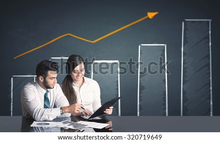 Successful business couple with positive business diagram in background  - stock photo