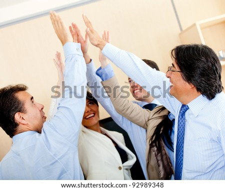 Successful business group giving a high-five at the office - stock photo