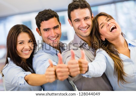 Successful business group with thumbs up at the office - stock photo