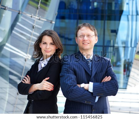 Successful business man and business woman standing over the modern background - stock photo