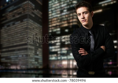 Successful business man at night with office buildings in the background - stock photo