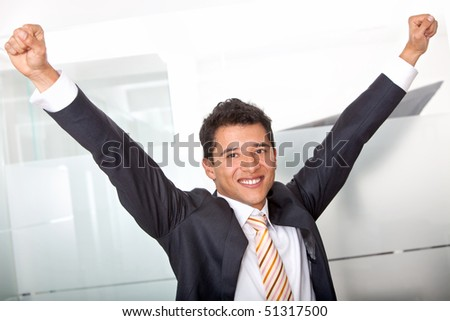 Successful business man at the office with arms up