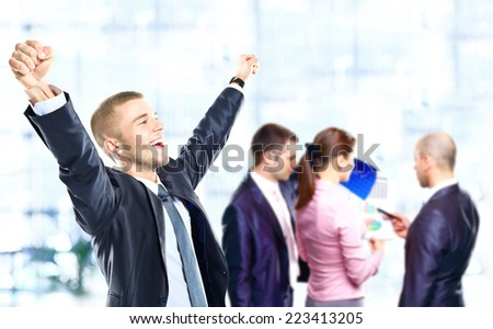 Successful business man celebrating with arms open - stock photo