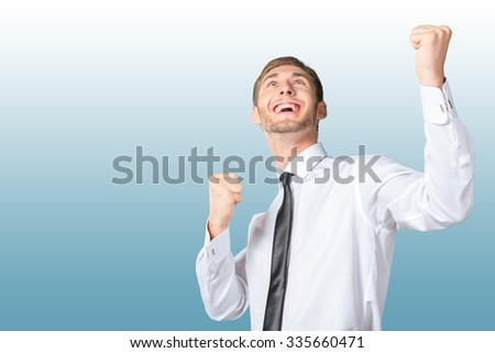 Successful business man celebrating with arms up
