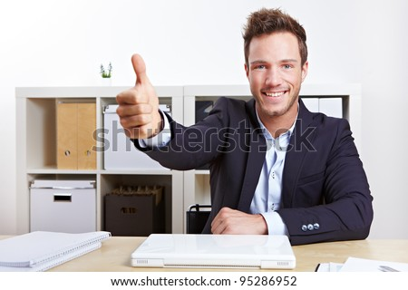 Successful business man in office holding his thumbs up - stock photo