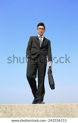 Successful business man look and smile to you with blue sky, asian male - stock photo