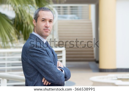 Successful business man looking confident and smiling, outside office - stock photo