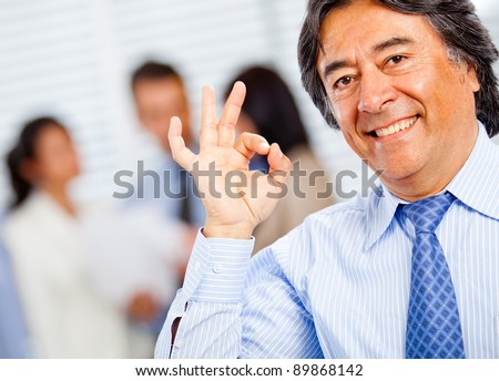 Successful business man making an ok sign with his hand - stock photo