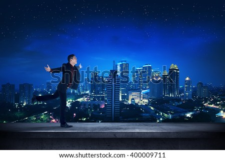 Successful business man on the rooftop at night time. Business success concept - stock photo