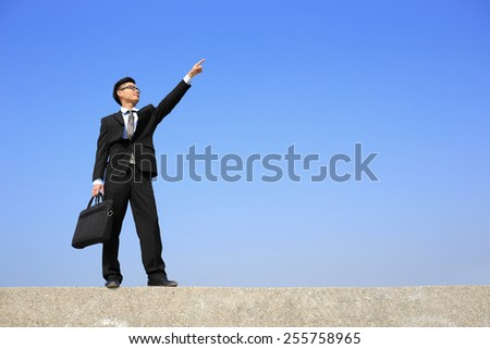 Successful business man pointing copy space in the image with blue sky, asian male