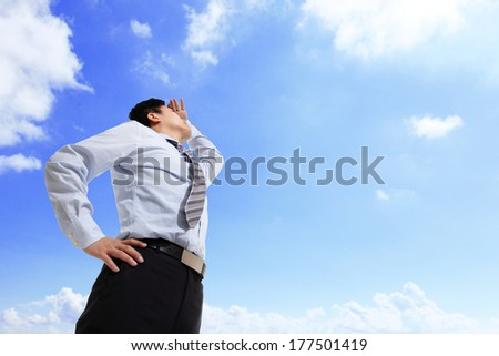 Successful business man purposefully looking away with blue sky, asian male - stock photo