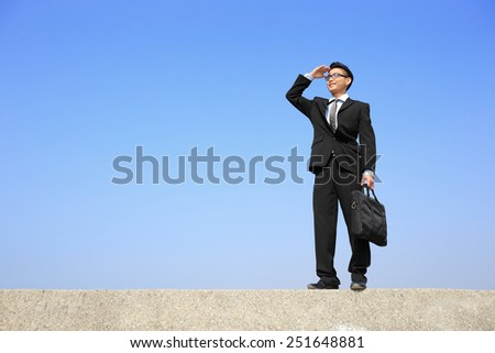 Successful business man purposefully looking away with blue sky, asian male