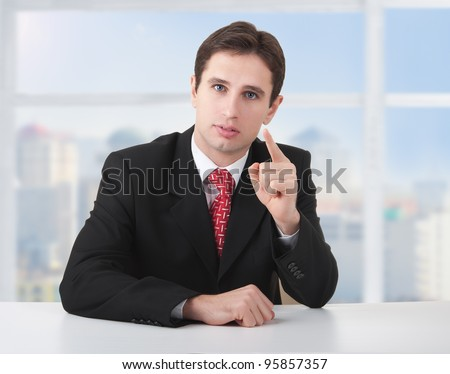 successful business man seriously sitting at a desk in his office and shows the index finger of the hand - stock photo