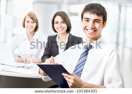 Successful business man sitting with his team at office - stock photo