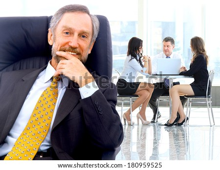 Successful business man standing with his staff in background at office - stock photo