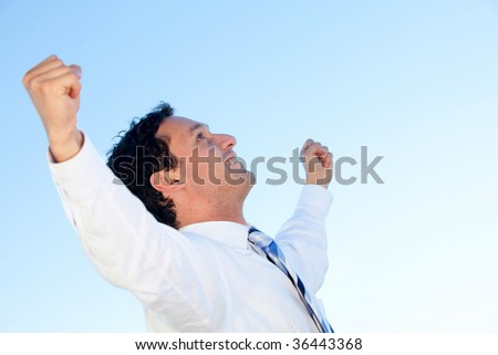 Successful business man with arms up smiling - stock photo