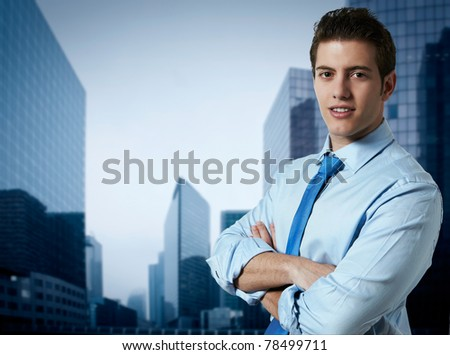 Successful business man with office buildings in the background - stock photo