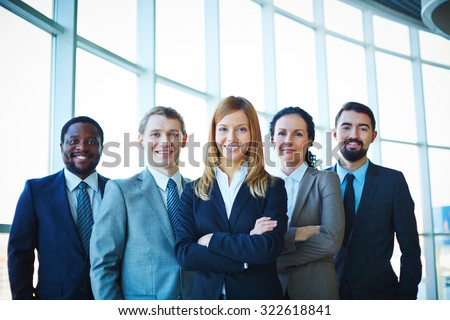 Successful business partners looking at camera with smiles - stock photo