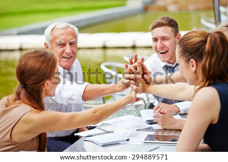 Successful business people doing high five in a meeting for motivation - stock photo