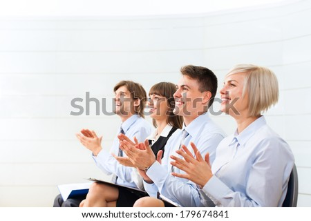 Successful business people group applauding after presentation, businesspeople applause sitting in row at the meeting office room on conference - stock photo