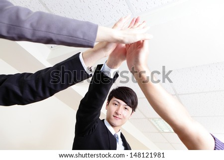 Successful business people group celebrating with hands giving high five at office, asian people