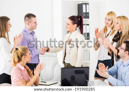 Successful business people shaking hands at the meeting because of Successful Agreement. Group of their colleague celebrating.