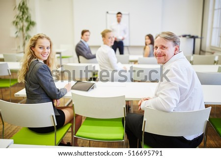 Successful business people sitting in a seminar and smiling content