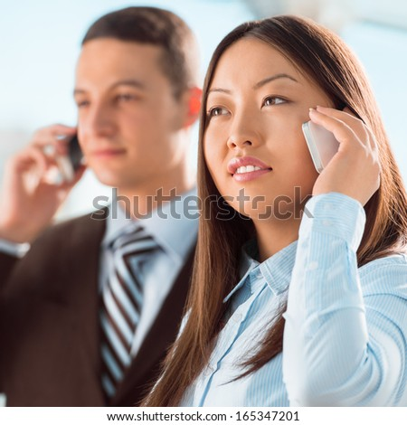Successful business people talking on cell phone while standing at office or hallway - stock photo