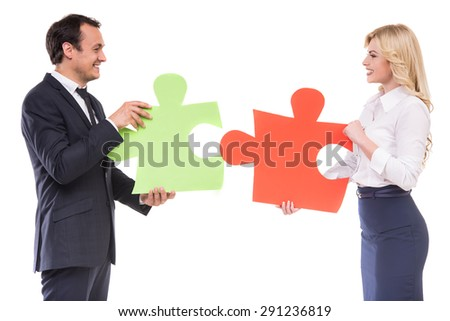 Successful business people wanting to put two big pieces of puzzle together. White background. - stock photo