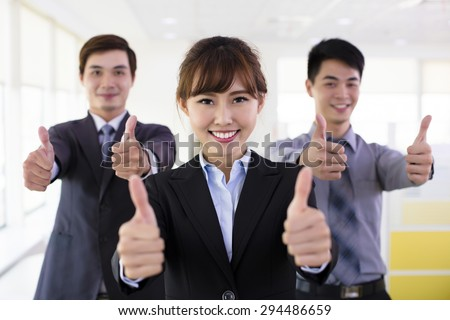 Successful business people with thumbs up - stock photo