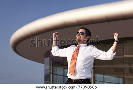 Successful business person in white shirt, orange tie and sunglasses raising his hands in front of office building and blue sky.